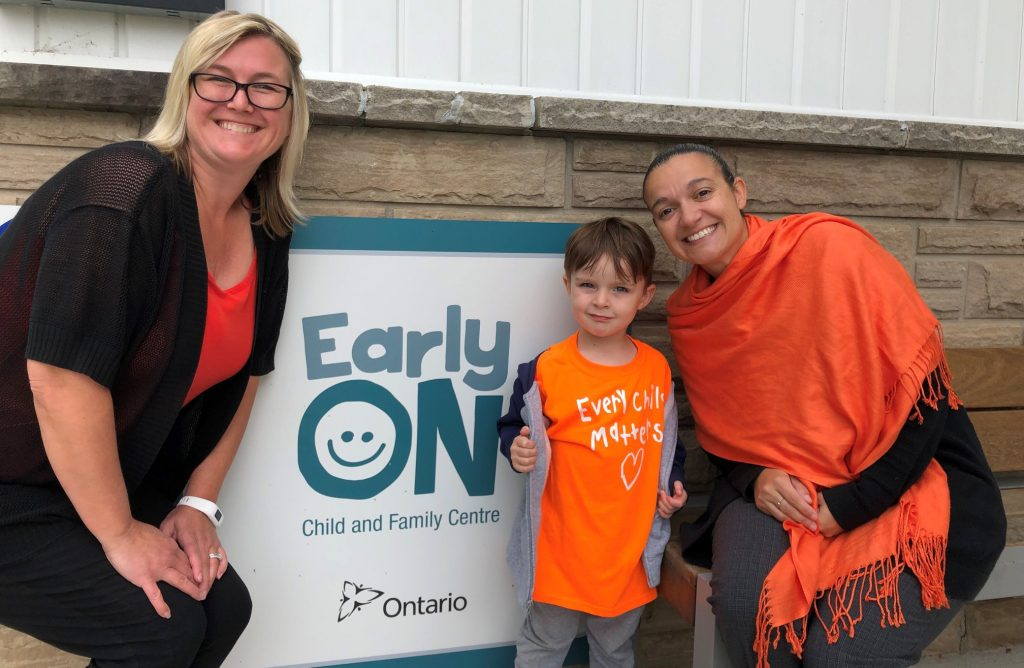 Two workers and a kid are posing near the sign of Early Years Centre Ontario