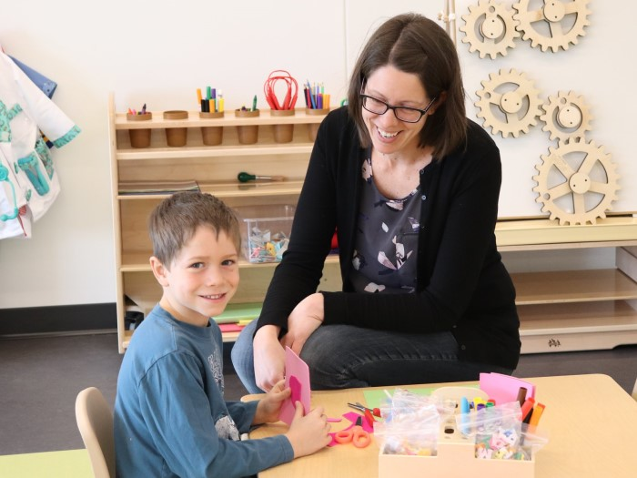 A kindergarten teacher is sitting near a boy who is doing a craft  in EarlyON Years Centre
