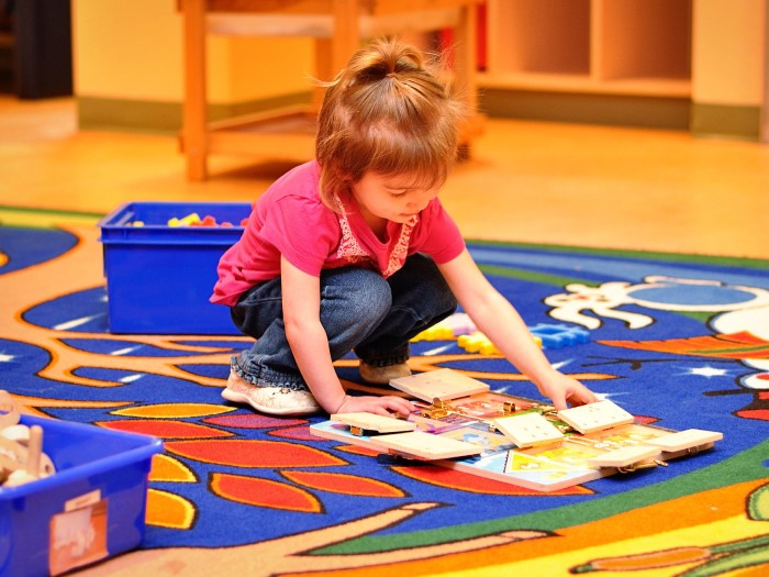 A little girl is looking at books whuch are laying on the carpet in EarlyON Years Centre