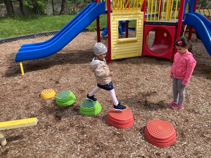 Two kids wearing hats and jackets are having fun on the playground in EarlyON Years Centre