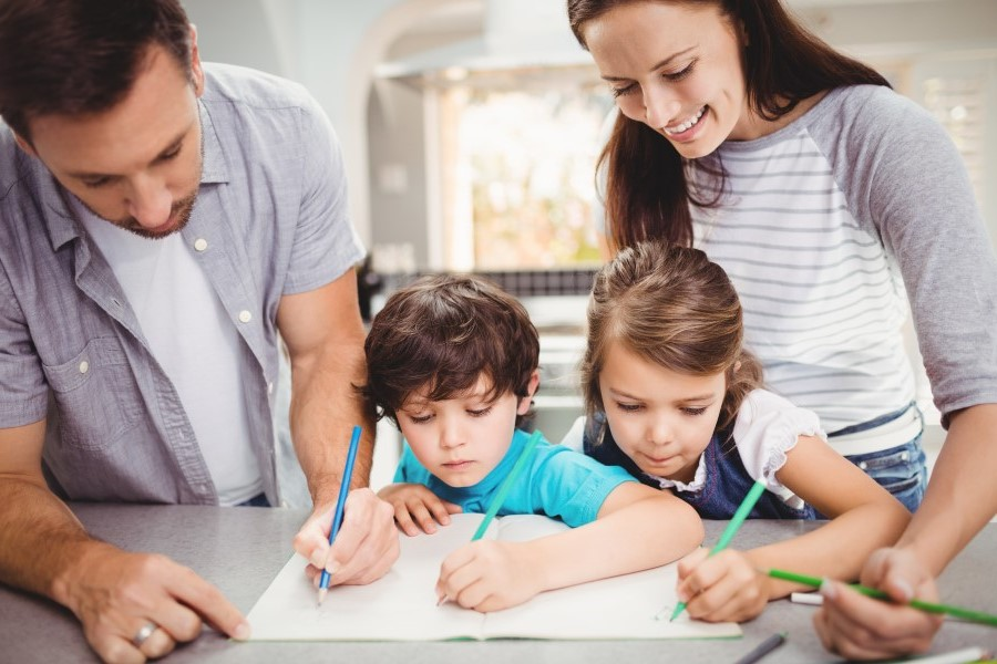 Parents with their daughter and son are writing in the copybook together
